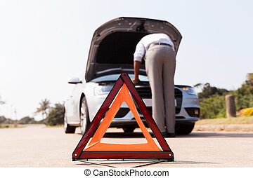 driver trying to figure out how to fix broken down car