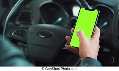 Driver using a smartphone inside the car. Chromakey smartphone with green screen. Auto navigation. Internet addiction. Automobile insurance application.