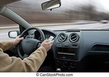 Driver using cell phone in car blurred motion