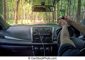 Driver's hands taking photo from smartphone inside of a car