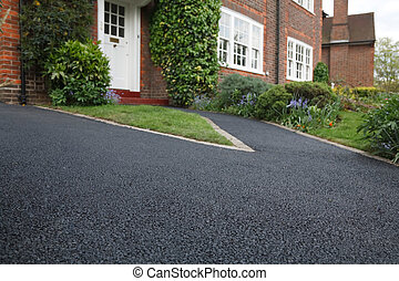 Driveway - New bitumen driveway outside a beautiful brick...
