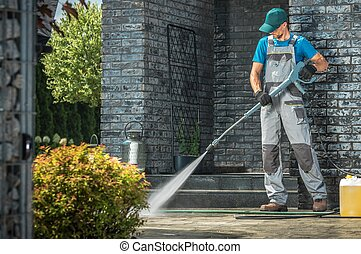 Driveway Pressure Washing. Caucasian Worker Cleaning Area in...