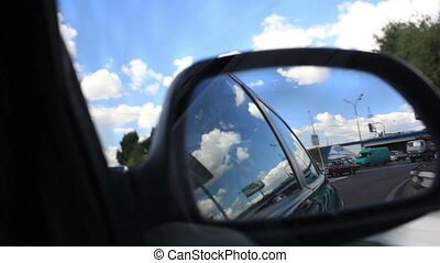 Driving a car in city with view from side mirror.