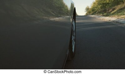 Driving a car is a country road. Wheel spinning POV