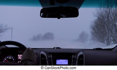 driving a car on a winter country road during a snow storm.