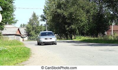 Driving a car through village