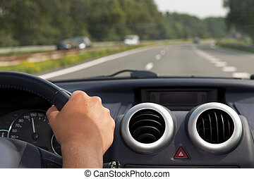 Driving a car with a hand on the steering wheel
