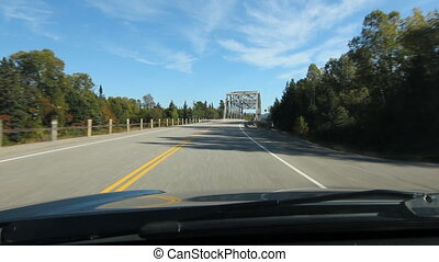 POV driving across a truss bridge. Driving across a truss bridge that crosses the Agawa River. Trans Canada HWY No 1 or Hwy ON-17 in Northern Ontario, Canada.