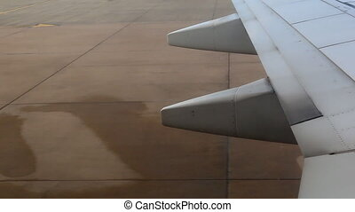 Driving airplane on the ground at airport. View of an aircraft wing moving along concrete runway.