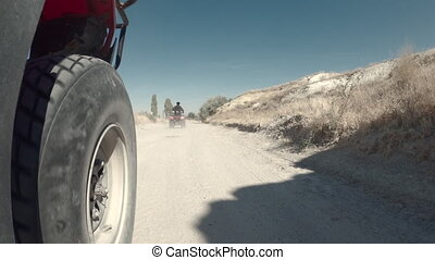 Driving along dusty road in Turkey, view from quad bike front wheel