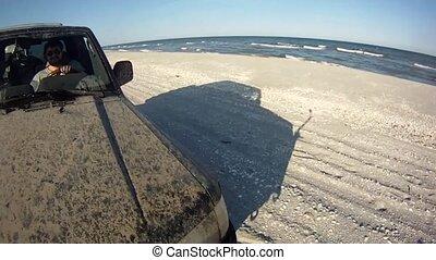 Driving along snowy beach