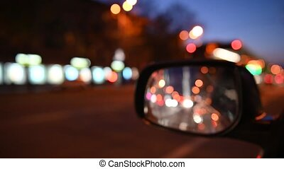 Driving at night. The view from the car on the side rearview mirror. blurred city lights. 4k