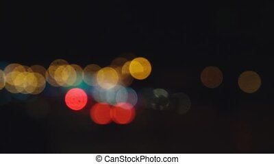 Driving at night. View the windshield and blurred cars in the city. window of the front car with a blurred city traffic on city streets.