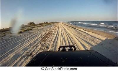 Driving at sunset, on the beach