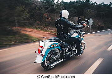 Driving blue motorcycle on the forest road