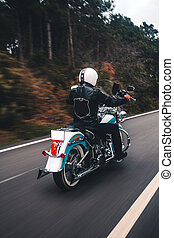 Driving blue motorcycle on the highway, back view