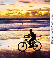 Driving bycicle on the beach