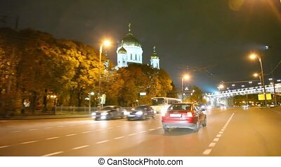 Driving car in night past the Cathedral of the Redeemer