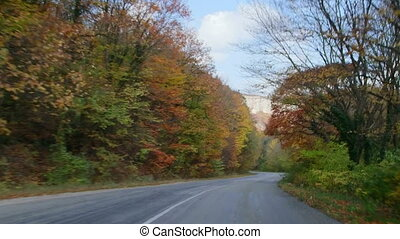 Driving car on mountain road through fall foliage