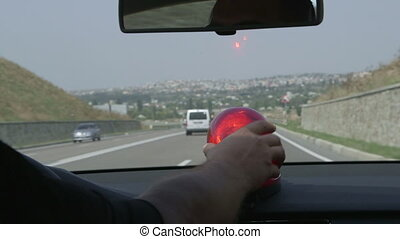 Driving car with red flashing light on highway