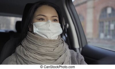 Driving car woman in the old factory going on the shift wearing pollution mask.