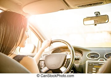 Driving car - Young beautiful black-haired woman driving car...