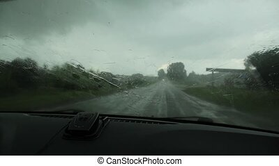 Driving in a nasty rainy day, view of the country road through the windshield during the car drive. Rain drops on window car windshield