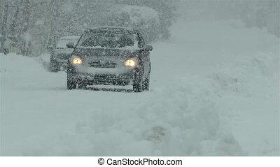 Winter season: a car passes by on a snow covered street under intense snowfall.