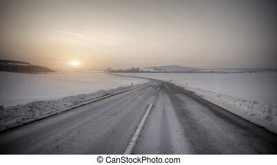 Driving in snow country with sunset