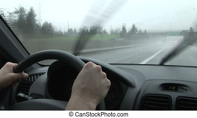 Woman driving car through the rain on a highway, windshield wipers working, Portland, Oregon