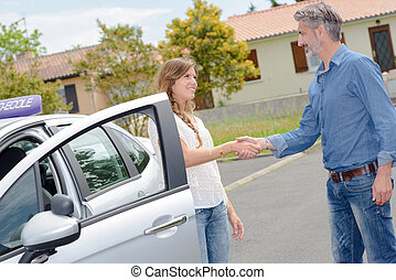 Driving instructor and student shaking hands