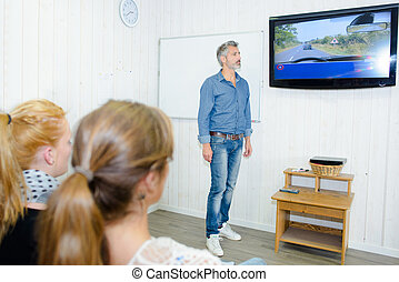 driving instructor standing in front of a screen