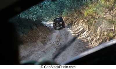 Driving old-fashioned off-road jeeps. Smooth footage from off road vehicle going uphill through a forest. Extreme auto tourism. Stabilized camera follows a jeep climbing up a mountain.