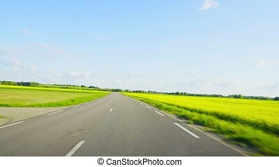 Driving on a country road between fields rapeseed