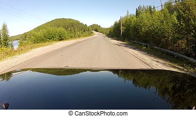 Driving on a highway along the forest