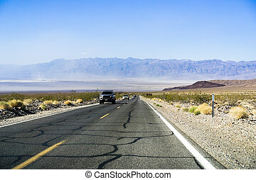Driving on a long, straight highway through Death Valley National Park, California