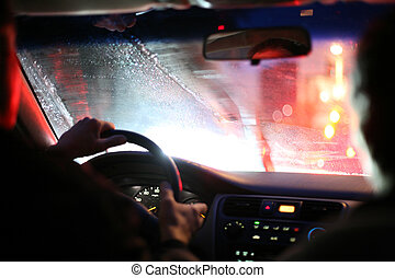 Driver and passenger driving on a rainy night in a city, view from inside. Shallow DOF.