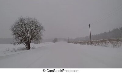 driving on a winter country road in a snow storm. back view