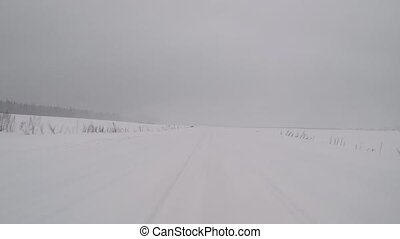 driving on a winter country road in a snow storm