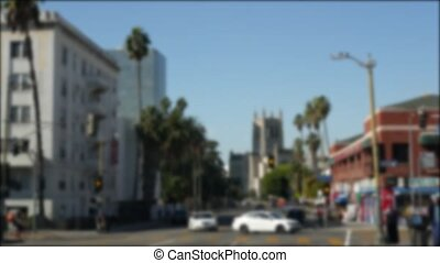 Driving on downtown streets of Los Angeles, California USA. Defocused view from car thru glass windshield on driveway. Blurred road with vehicles in Hollywood. Camera inside auto, LA city aesthetic.