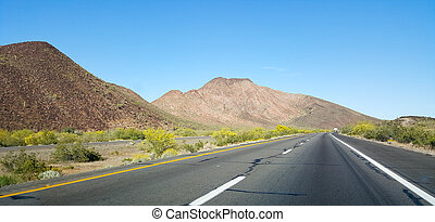 Buttes and low rise mountains along Interstate-10 east of city of Quartzsite. in Arizona desert covered with drought and extreme heat resistant vegetation.