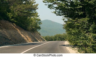 Driving On Mountain Road Through Forest With Turns. Driving On An Empty Road On a Bright Summer Day In Mountains