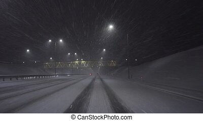 Driving on the highway at night in the snow