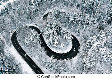 Driving on winter roads trough a forest winding road in the mountains