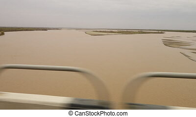 Driving past a muddy body of water - A wide POV shot,...