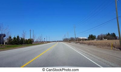 Driving Rural Road Along Farmland During Spring Day. Driver...