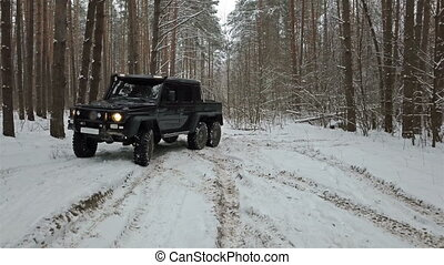 Driving SUV 6x6 by the off-road in the winter forest, front left view