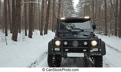 Driving SUV 6x6 by the off-road in the winter forest, front view