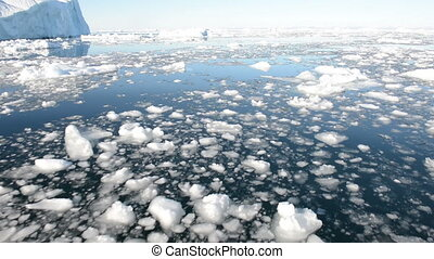 Driving through ice in arctic waters with icebergs in the background