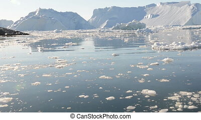 Driving through ice in arctic waters with icebergs in the...